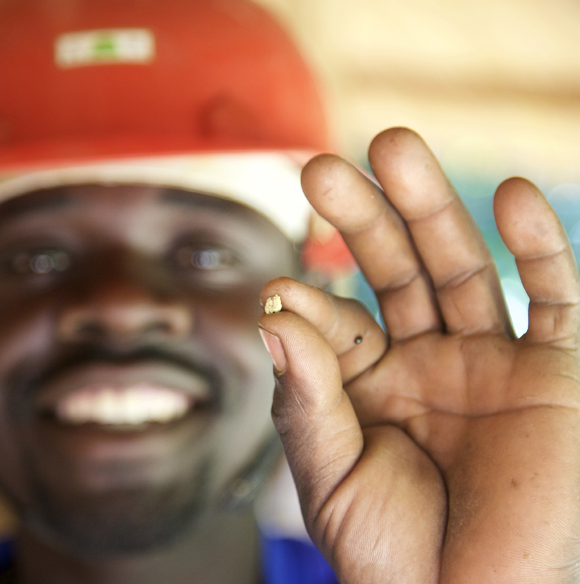 A small-scale gold miner in Uganda holds up a tiny nugget of gold.
