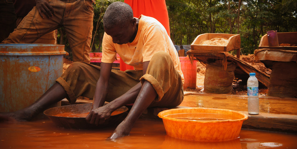 A Tanzanian gold miner mixes gold dust, mercury, and water by hand to form a mercury and gold amalgam. This is common practice in small-scale gold mining.