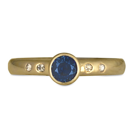 This Fairtrade Gold engagement ring features a sapphire and accent diamonds.